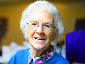 older woman with white hair and glasses wearing blue sweater