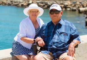 photo of older man and woman sitting next to a harbor
